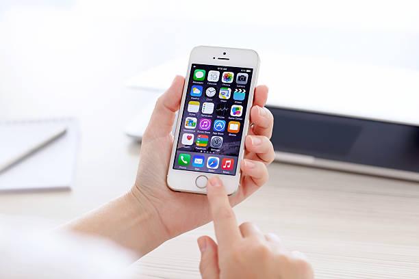 iPhone 5 Jahren mit IOS 8 in hand auf Hintergrund MacBook – Foto
