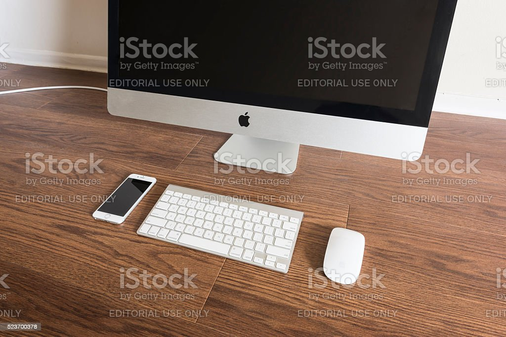 iPhone 6s placed next to iMac 27inch stock photo