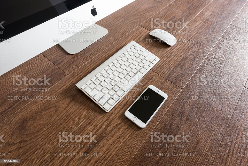 iPhone 6s placed next to iMac stock photo