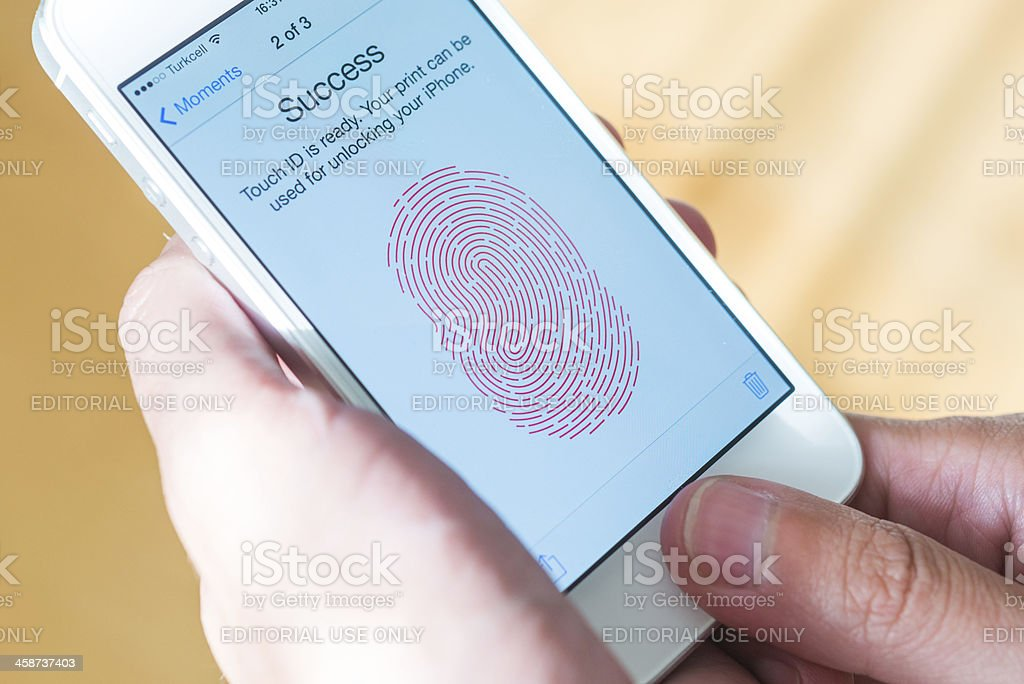 """iphone with fingerprint identity future """"Ankara, Turkey - September 20, 2013: Hand of a man with a white iphone with ios 7. You see the homepage of ios 7 fingerprint identity future."""" Apple Computers Stock Photo"""