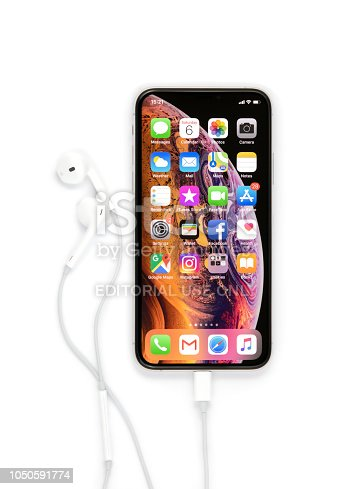 Celje, Slovenia - October 06, 2018: Front side of iPhone XS smartphone (with 5.8 inch Retina display, silver color version with 256 GB memory) with pluged in earpods, isolated on white.