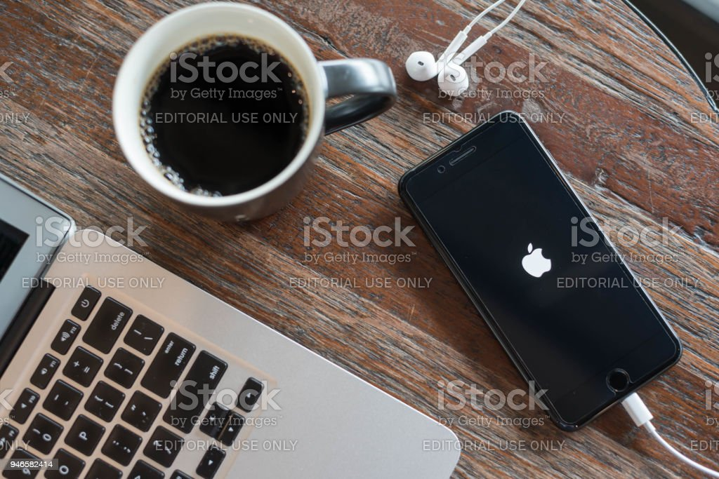 BANGKOK, THAILAND - NOVEMBER 26, 2016: Iphone7 Plus jet black serie on opening screen of Apple inc. icon with macbook air