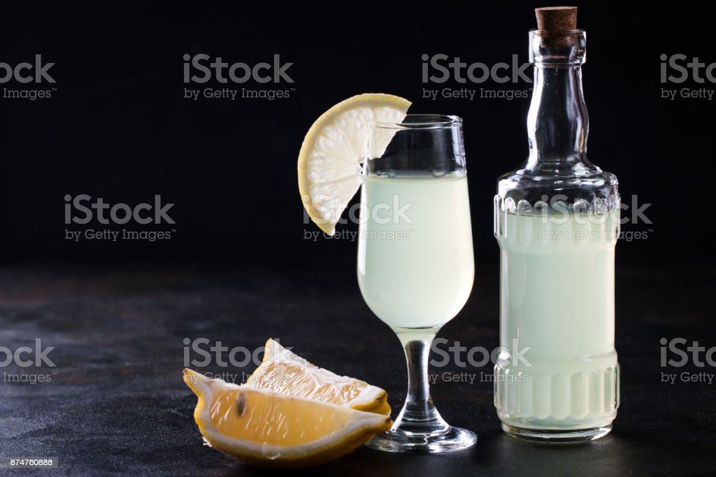 Iralian traditional liqueur with lemons on the vintage table, selective focus stock photo