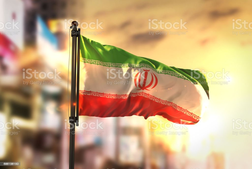 Iran Flag Against City Blurred Background At Sunrise Backlight stock photo