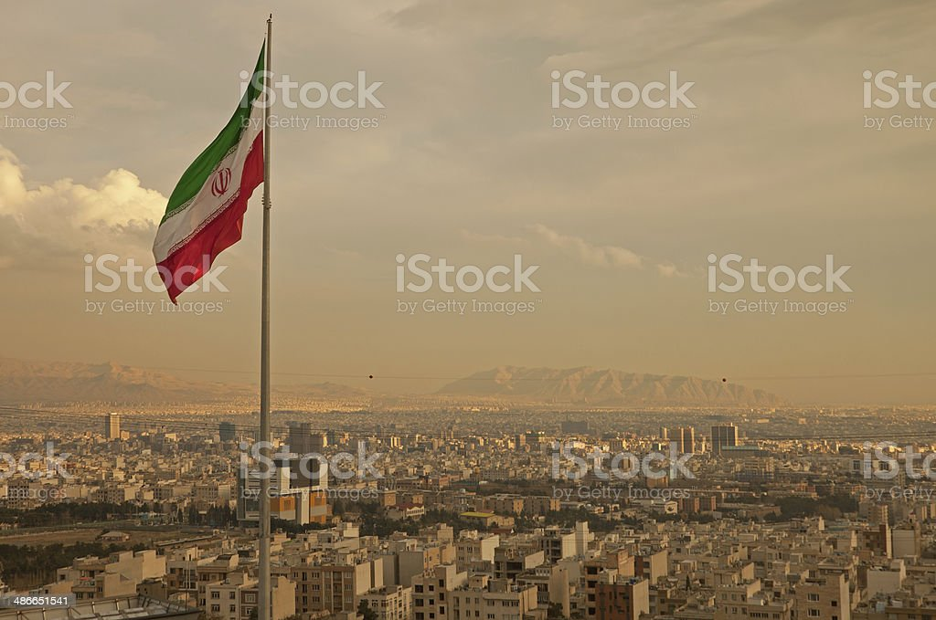 Iran Flag in the Wind Above Skyline of Tehran stock photo