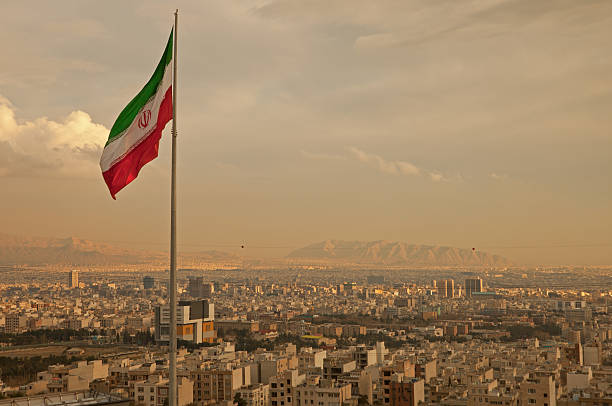 iran flagge im wind über die skyline von teheran - iranische stock-fotos und bilder