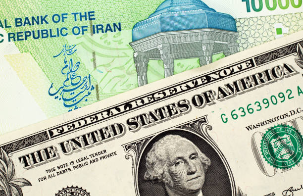 Iranian 10000 Rial Note With American One Dollar Bill A Green 10000 Iranian Rial Note With An American One Dollar Bill sanctions stock pictures, royalty-free photos & images