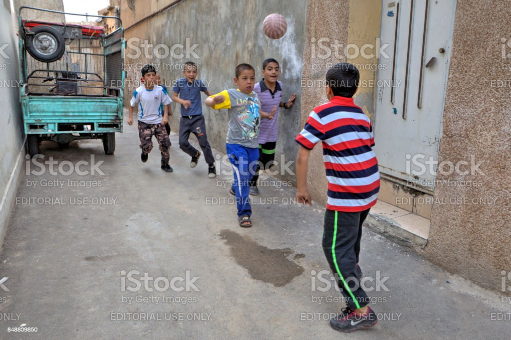 Iranian boys playing football in yard stock photo