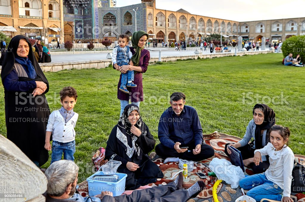 Iranian family is resting of square Naghshe Jahan, Isfahan, Iran. stock photo