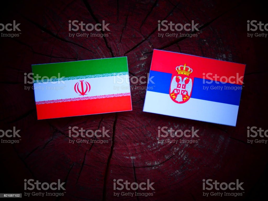Iranian flag with Serbian flag on a tree stump isolated - fotografia de stock