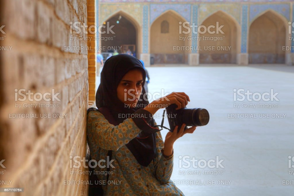 Iranian girl on travel photographed with her camera in Mosque. stock photo