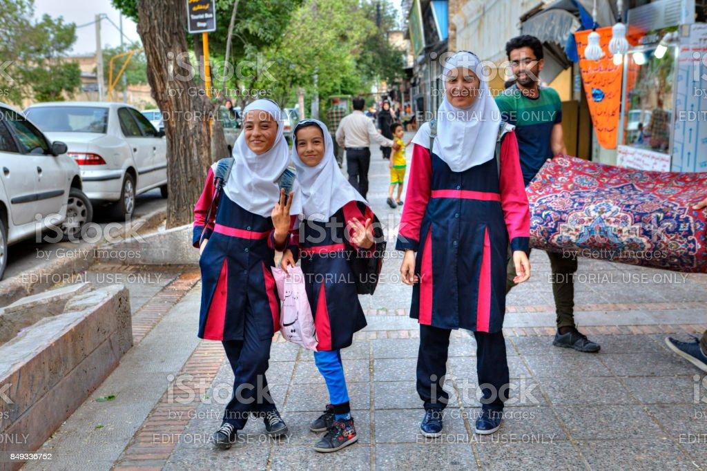 Iranian girls in school uniform on a city street. stock photo