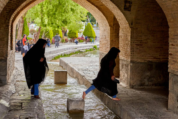 Jeunes filles iraniennes enjamber la circulation de l'eau sous le pont, Ispahan. - Photo