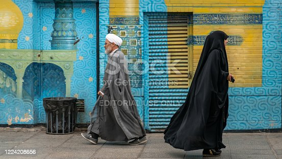 Qom, Iran - May 2019: Iranian man and woman in black dress walking in a street in the sacred city of Qom