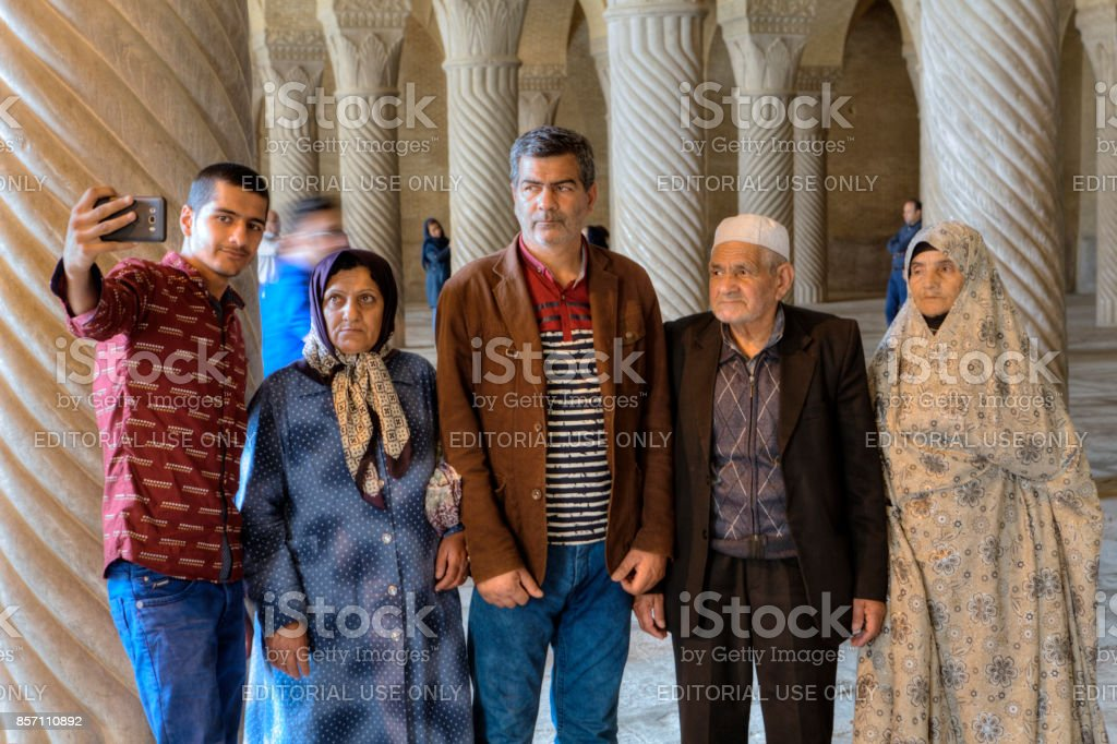 Iranian man makes selfie with his family in the mosque. stock photo