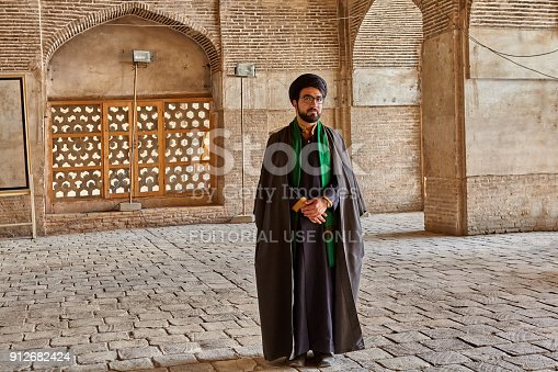 Isfahan, Iran - April 24, 2017: Iranian mullah in traditional clothes stands in the courtyard of the mosque.