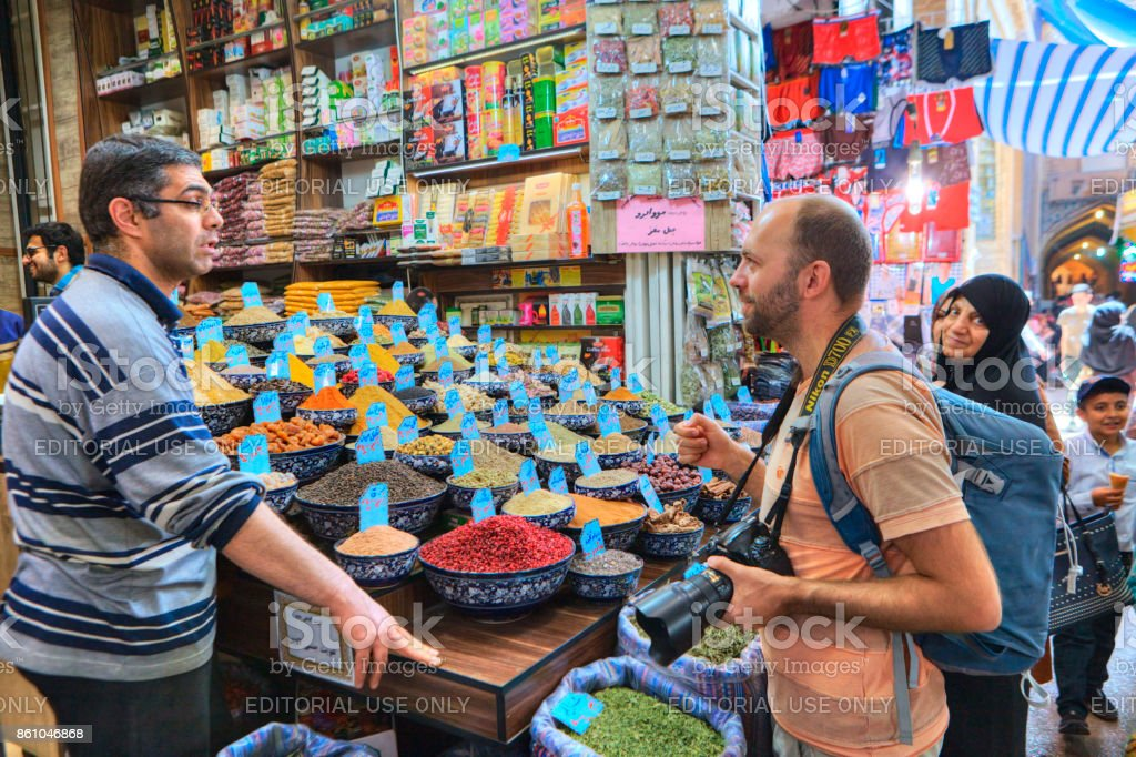 Iranian trader spices and grains communicates with buyer, Shiraz, Iran. stock photo