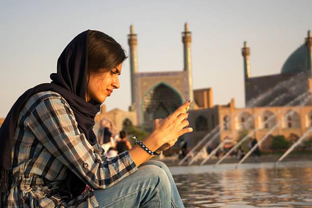 iranian woman checking her mobile phone - iranische stock-fotos und bilder