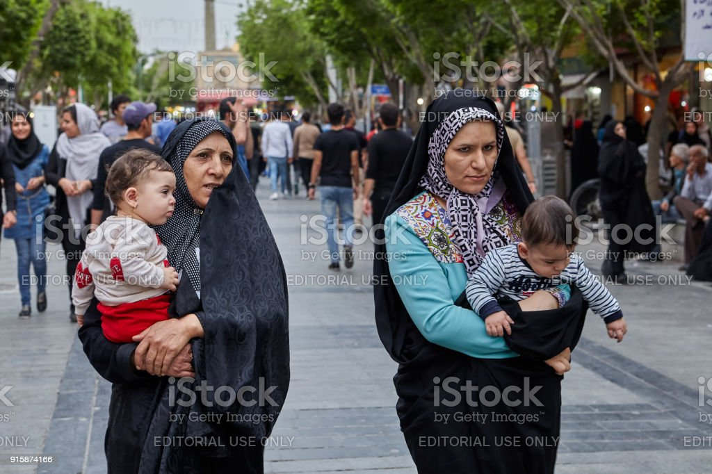 Iranian women walk down the street, Tehran, Iran. stock photo