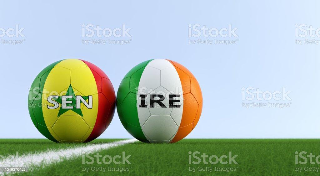 Irlanda vs Senegal partida de futebol - bolas de futebol na Irlanda e Senegal cores nacionais em um campo de futebol. Cópia espaço no lado direito - 3D Rendering - foto de acervo