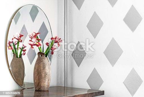 Iris flowers in a scratched ceramic vase at the mirror on the  wall with abstract rhombic pattern on stucco surface.