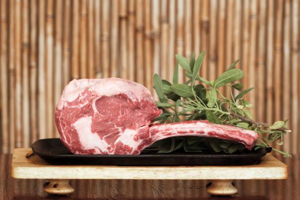 irish black angus tomahawk steak mit salbeiblättern - wie alt werden kühe stock-fotos und bilder