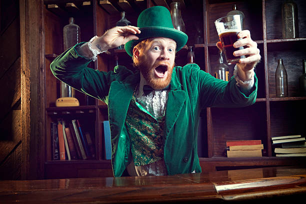irish character / leprechaun celebrating with pint of beer - st patricks days stock photos and pictures