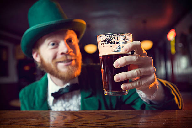 irish character / leprechaun making a toast with beer - happy st. patricks day stock photos and pictures