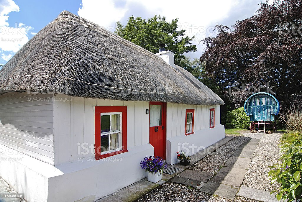 Irish cottage with straw thatched roof and romany gypsy caravan stock photo