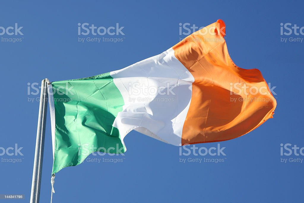 Irish flag blowing in the wind on blue sky stock photo