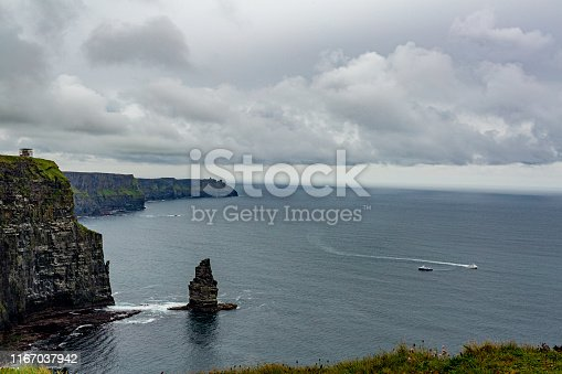Irish landscape of the Branaunmore sea stack and two boats sailing in the ocean on the Cliffs of Moher, geosites and geopark, Wild Atlantic Way, wonderful spring cloudy day in County Clare in Ireland