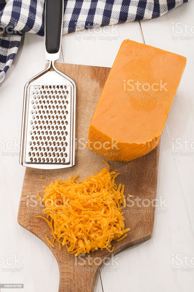irish mature grated cheddar cheese on a wooden board stock photo