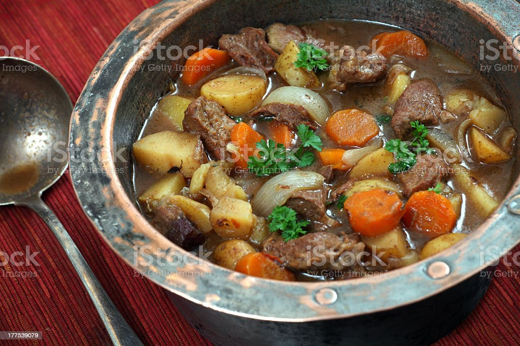 Irish stew in copper bowl, with vintage spoon stock photo