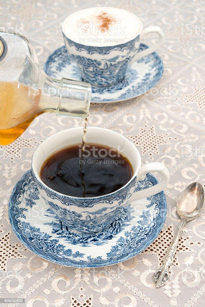 Irish whiskey being poured into black coffee to make Irish coffee. stock photo