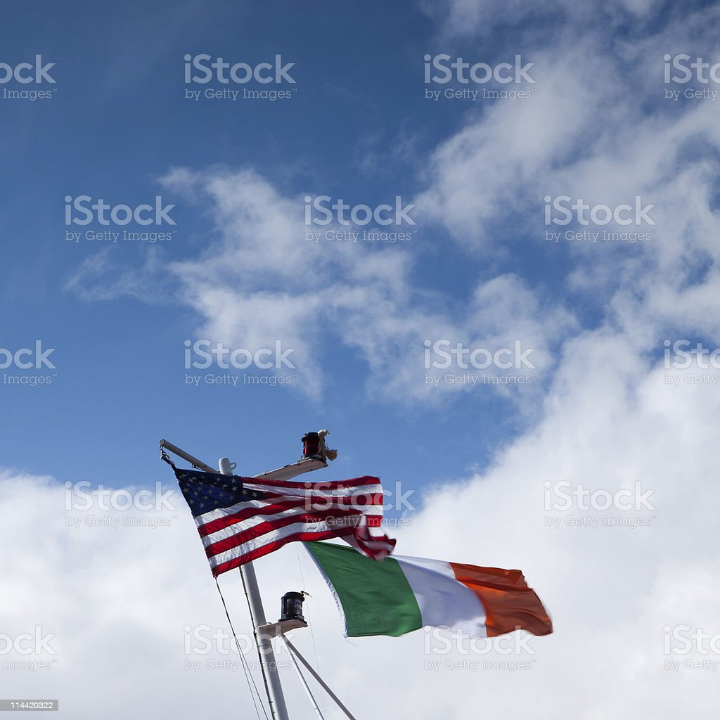 Irleand and US flags on top of mast over sky stock photo