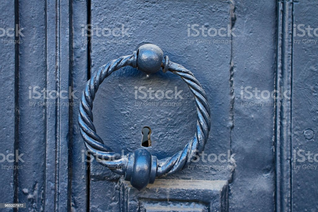Iron antique door handle in the form of a twisted ring royalty-free stock photo
