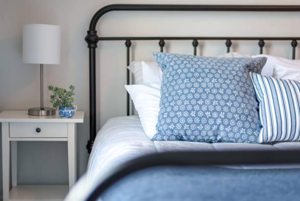 eisenbett mit blauen und weißen betten-modernes bauernhaus - bauernhaus bett stock-fotos und bilder