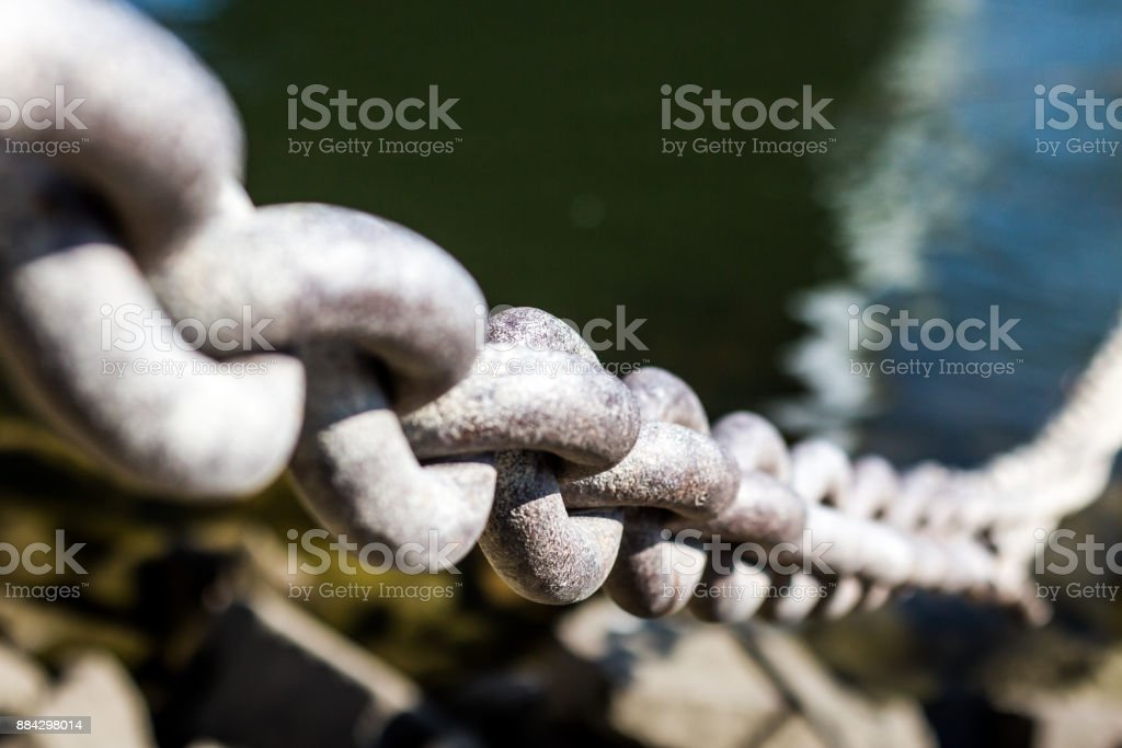 Iron chain on the riverbank stock photo