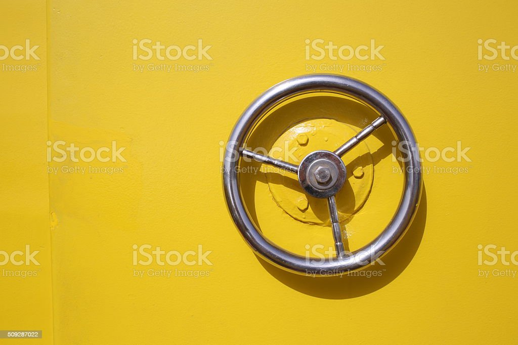 Iron circle wheel on the door of yellow ship stock photo