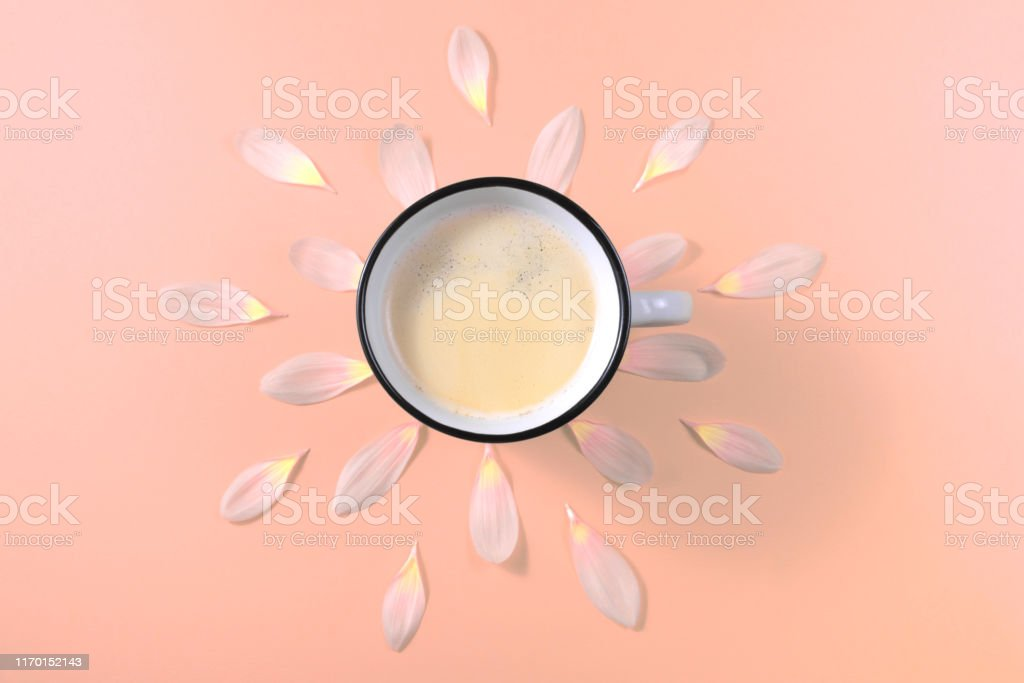 iron Cup with black coffee with flower petals on pink background
