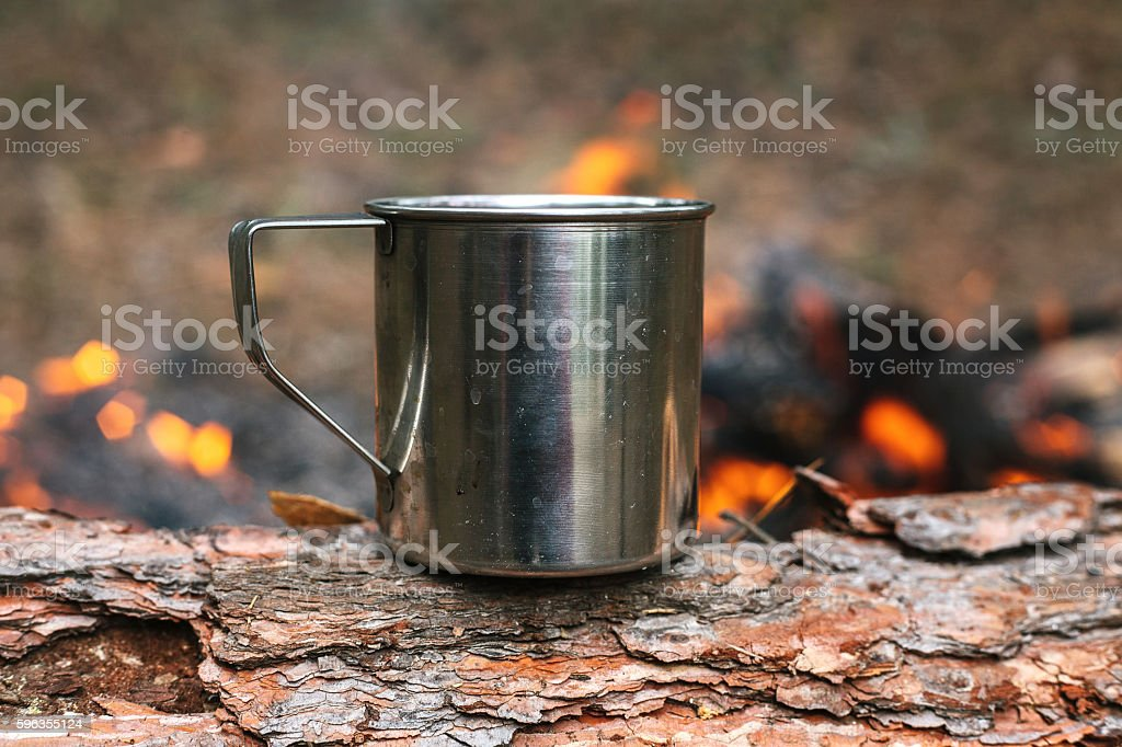 Iron cup with hot tea. Journey into the wild concept. royalty-free stock photo