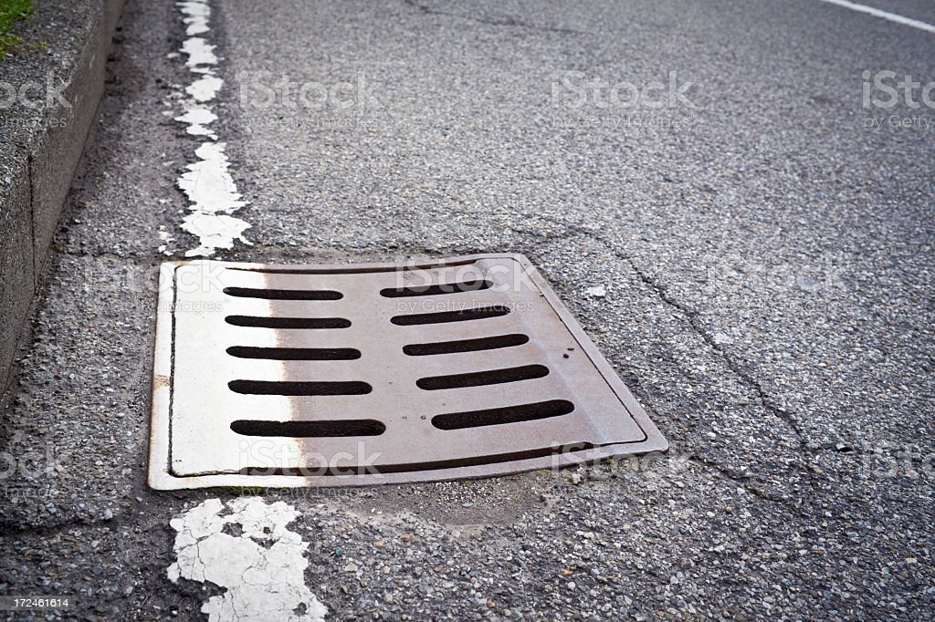 Iron Drain Cover With White Line On Asphalt royalty-free stock photo