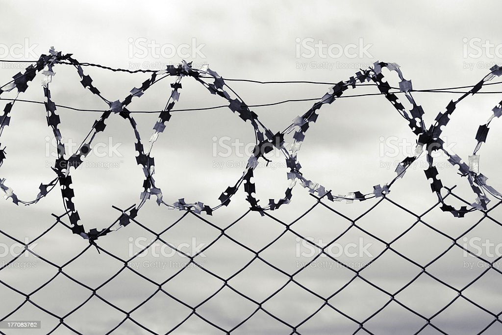 Iron fence with a barbed wire. royalty-free stock photo