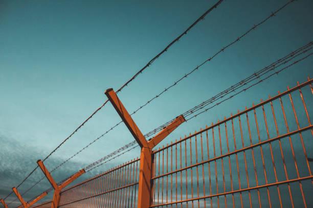 Eisenzaun mit Stacheldraht während der blauen Stunde – Foto