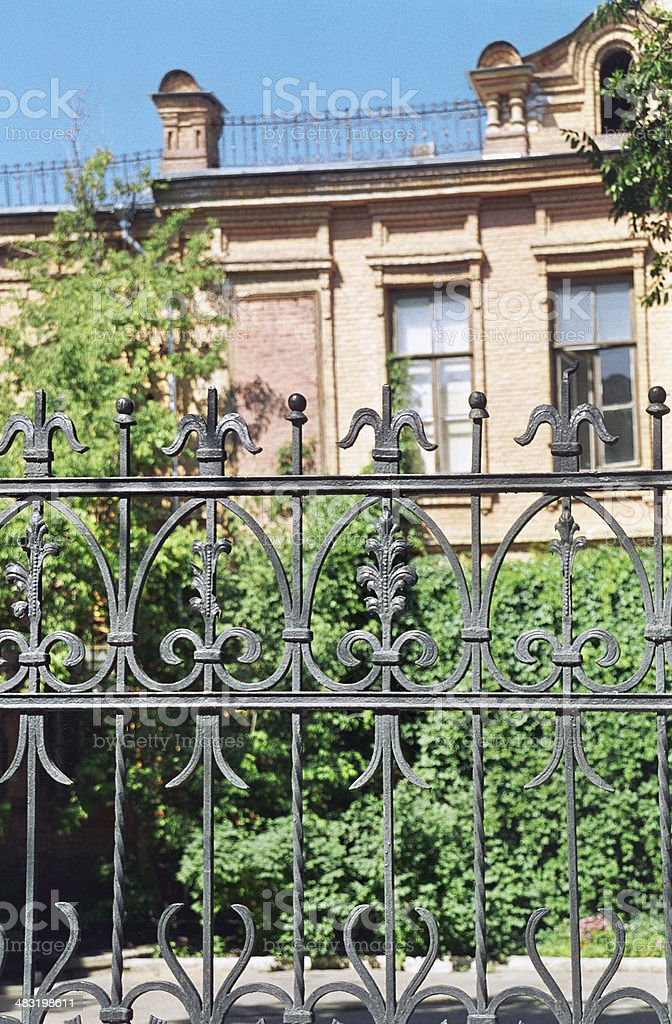 Artistic iron fence before the yard of the old house. The end of the...