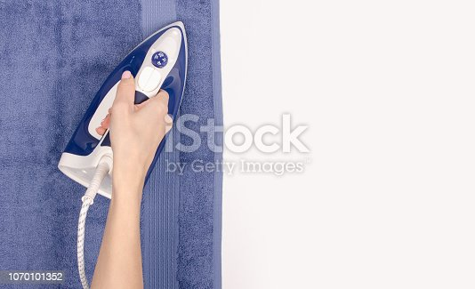 istock Iron in hand towel close up macro on a white background 1070101352