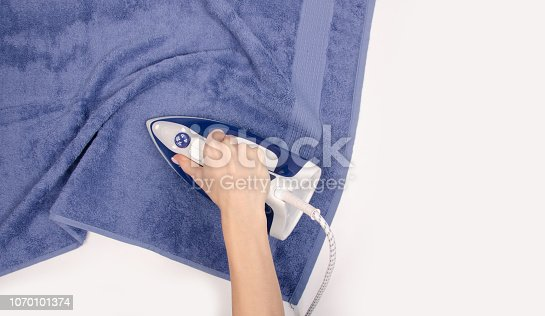 istock Iron in hand towel close up macro on a white background 1070101374