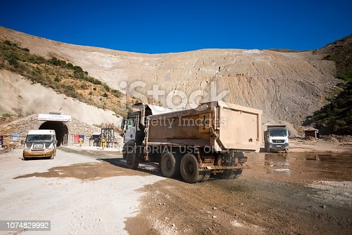 Kayseri, Turkey - July 20, 2017 : The entrance of an iron mine tunnel in Kayseri Turkey. Trucks carry iron out.