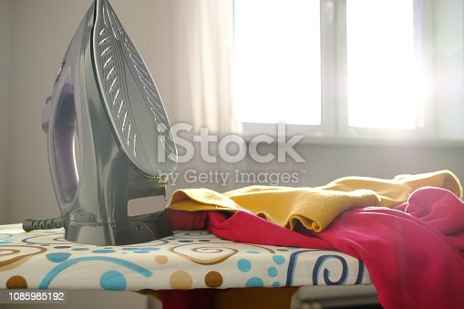 istock Iron on the ironing board 1085985192