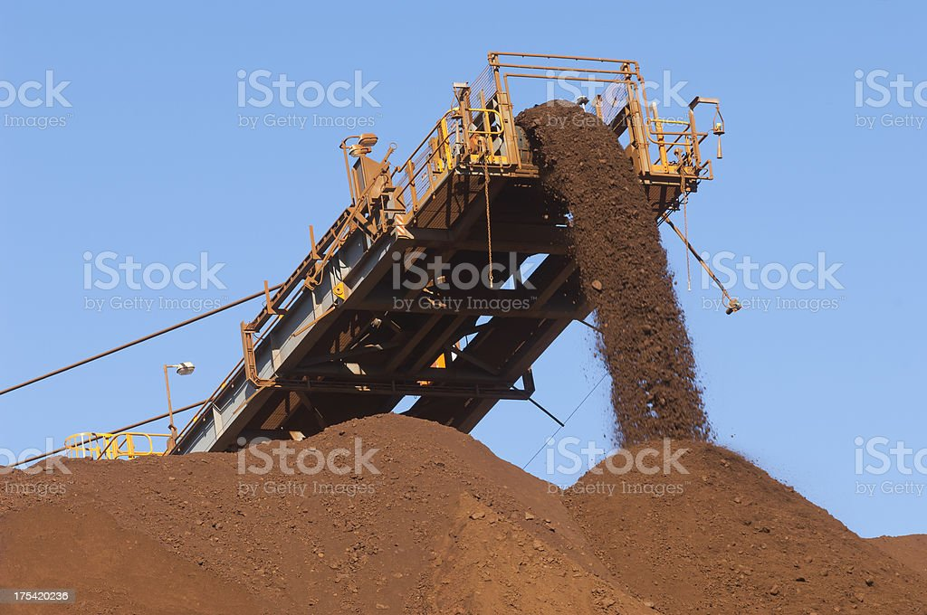 Iron ore being loaded onto a stockpile. stock photo